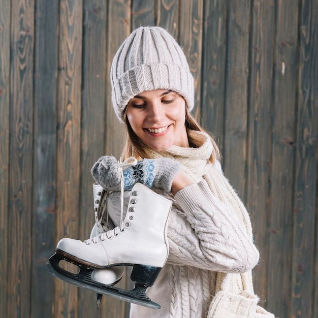 Woman in sweater with skates behind back Free Photo