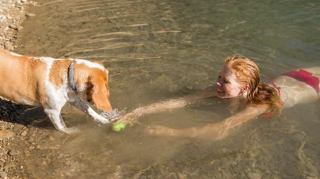 Donna che nuota e gioca con la vista alta del cane Foto Gratuite