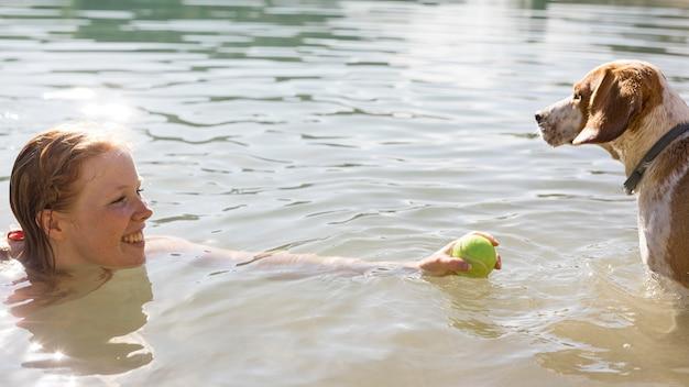 Donna che nuota e gioca con la vista laterale del cane Foto Gratuite