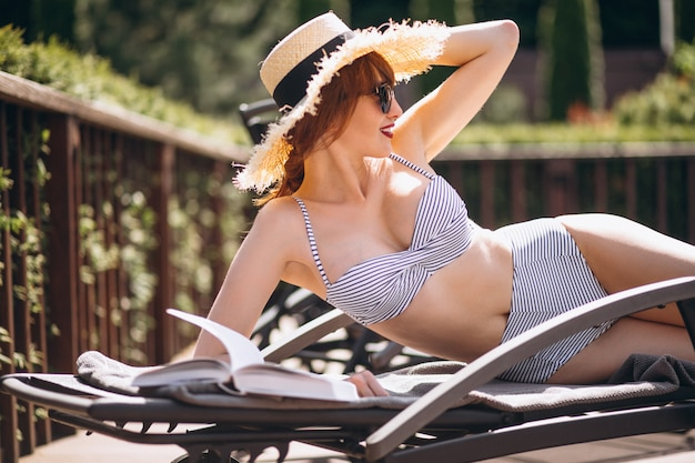 Woman in swimming suit lying on a bed and reading a book Free Photo