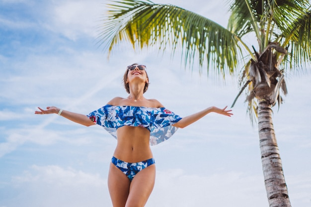 Woman in swimming suit standing at the beach near the palm Free Photo
