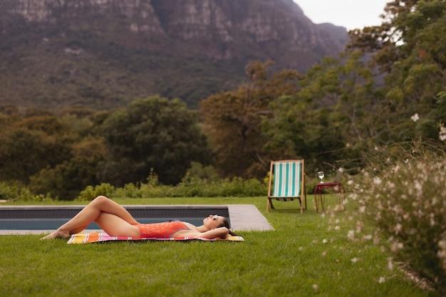 Woman in swimwear relaxing near poolside in the backyard Free Photo