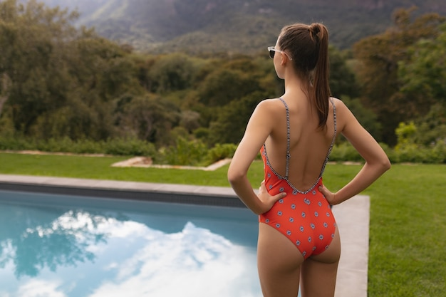 Woman in swimwear standing with hands on hip near poolside in the backyard Free Photo