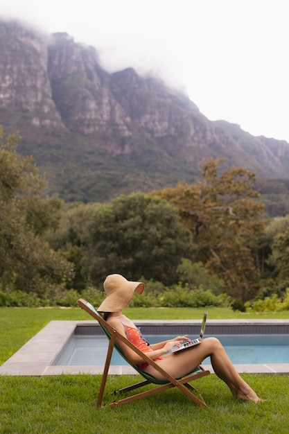 Woman in swimwear using laptop on a sun lounger near poolside in the backyard Free Photo