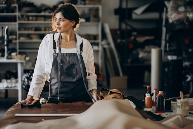Woman tailor working on leather fabric Free Photo