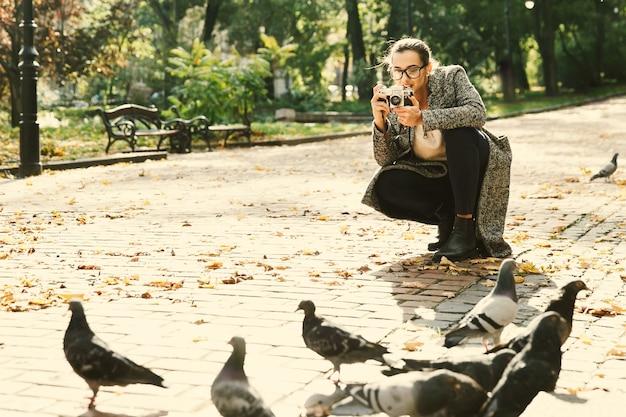 Женщина берет фотографию голубей, стоящих в парке Бесплатные Фотографии
