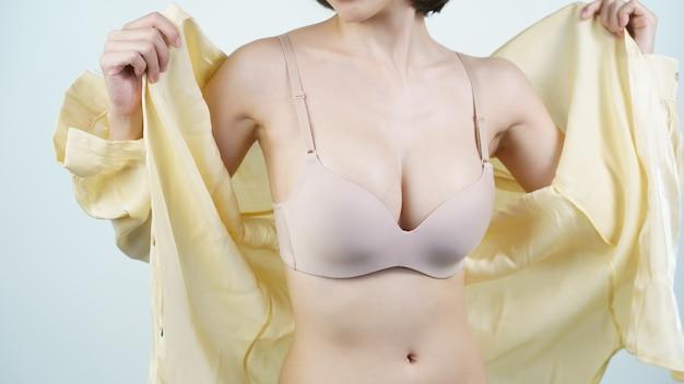 여자는 밝은 누드 란제리 유방 임플란트 수술 개념에 그녀의 밝은 노란색 셔츠를 벗고 프리미엄 사진