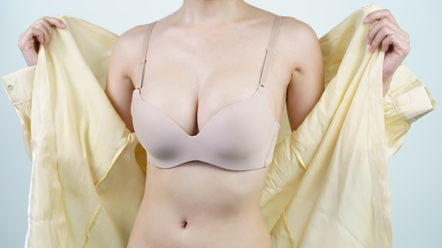 Woman takes off her light yellow shirt, she is in light nude lingerie. breast implant surgery concept. Premium Photo