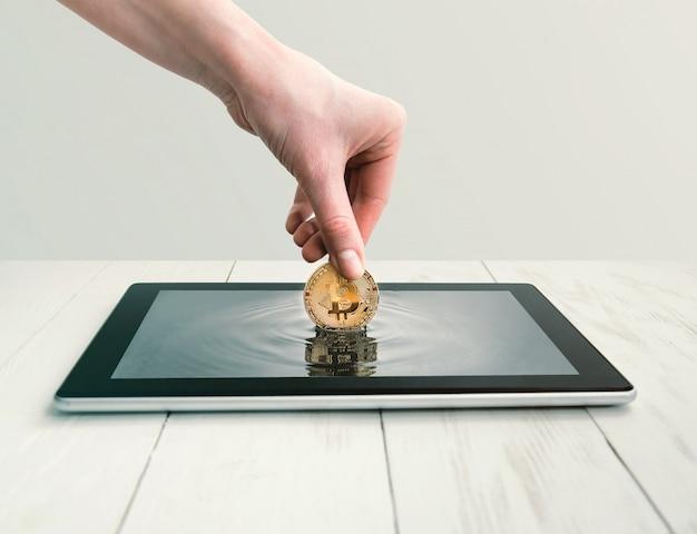 Женщина достает биткойны с экрана планшета. Premium Фотографии