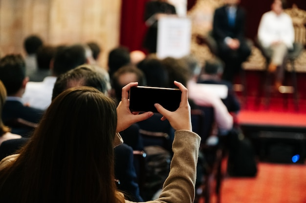 Woman takes a picture with a mobile phone in a meeting Premium Photo