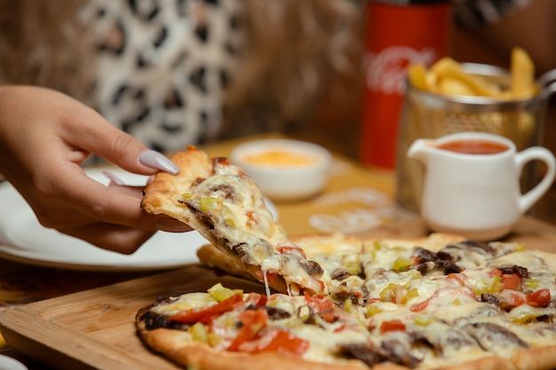 Woman takes a slice of pizza Free Photo