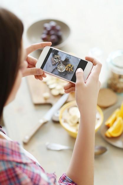 彼女の健康的な朝食の写真を撮る女性 無料写真