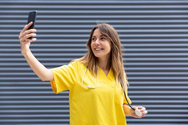 看護師の制服を着た携帯電話で写真を撮る女性 Premium写真