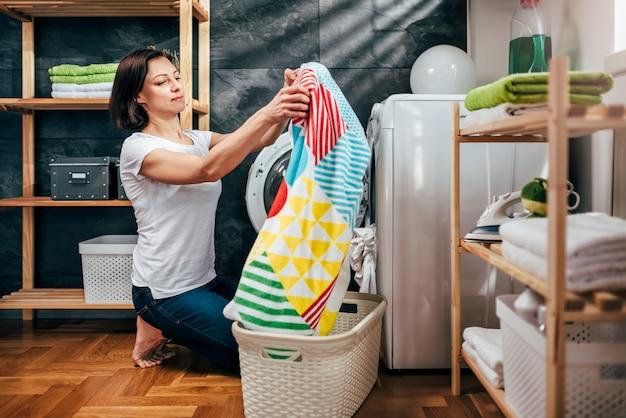 Woman taking clothes out washing machine Premium Photo