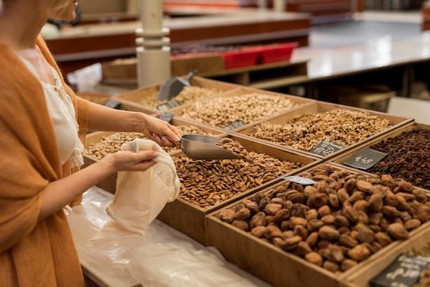 市場の場所で乾燥食品を取る女性 無料写真