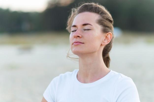 Donna che cattura la fresca brezza dell'oceano sulla spiaggia durante l'allenamento Foto Gratuite