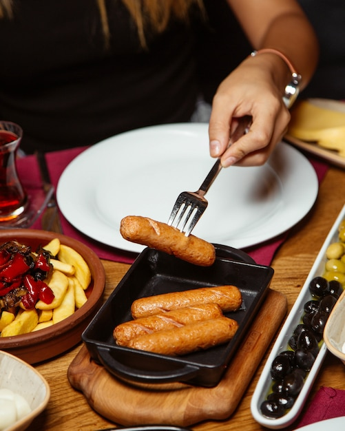 Женщина берет жареные колбаски из маленькой чугунной сковороде Бесплатные Фотографии