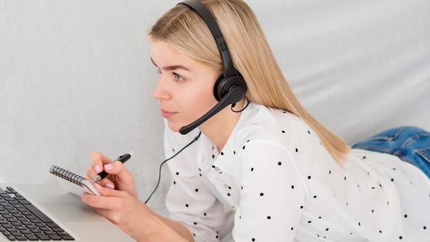 オンラインコースからメモを取る女性 Premium写真