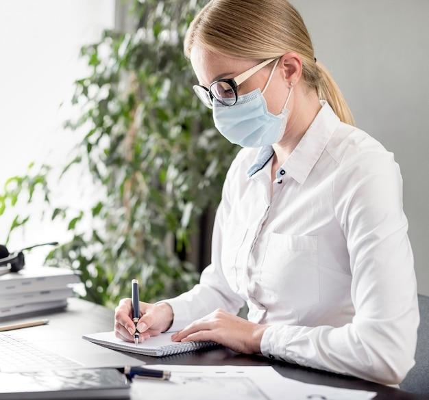 フェイスマスクを着用しながらメモを取る女性 無料写真