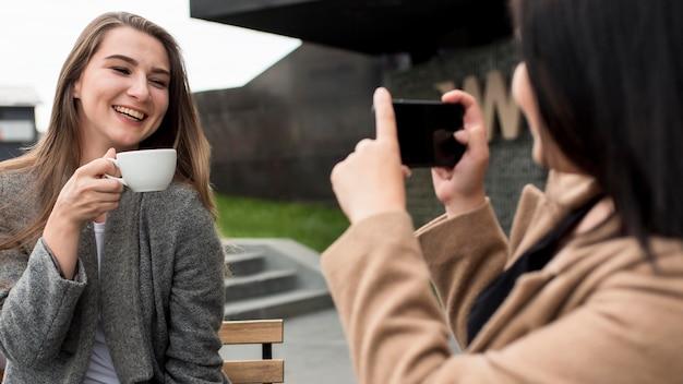 Donna che cattura una foto della sua amica che tiene una tazza di caffè Foto Gratuite