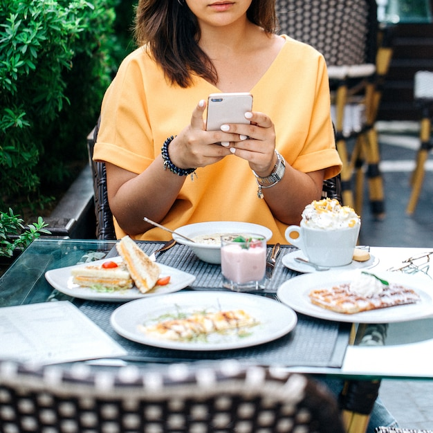 Woman taking photo of table with food Free Photo