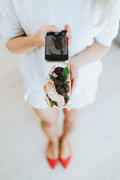 Woman taking a photo of a toast with blackberry jam and vegan cream cheese Premium Photo