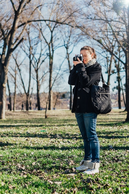 Woman taking a photo with old analog camera Premium Photo