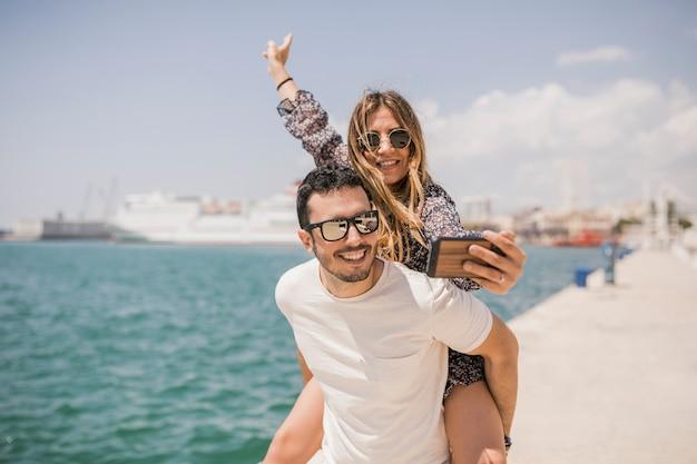 Woman taking photograph of her boyfriend enjoying piggyback ride on his back Free Photo