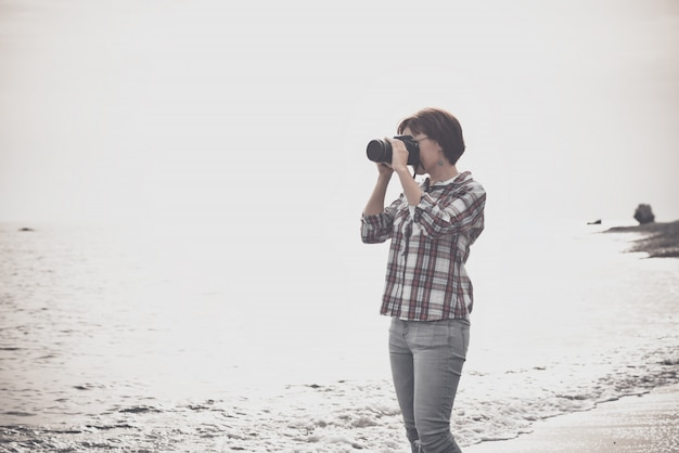 Woman taking photographs with dslr on the beach Premium Photo