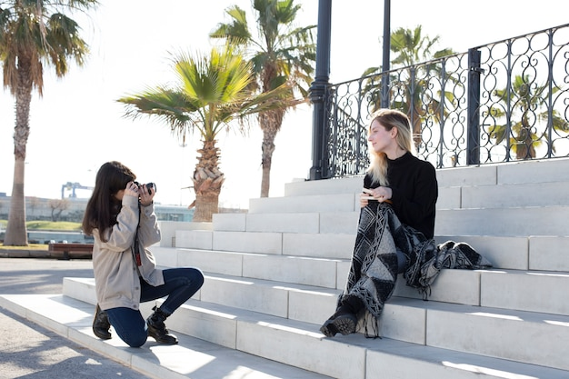 Woman taking photos of charming girlfriend Free Photo