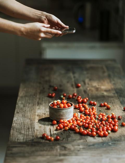 Woman taking photos of red cherry tomatoes Premium Photo