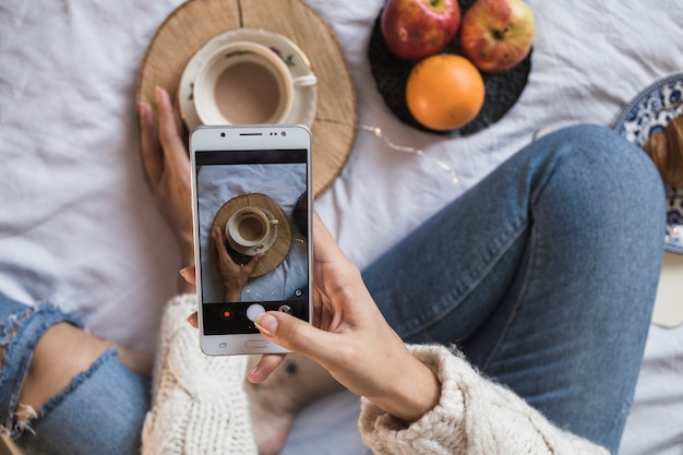 Woman taking picture of coffee with smartphone Free Photo