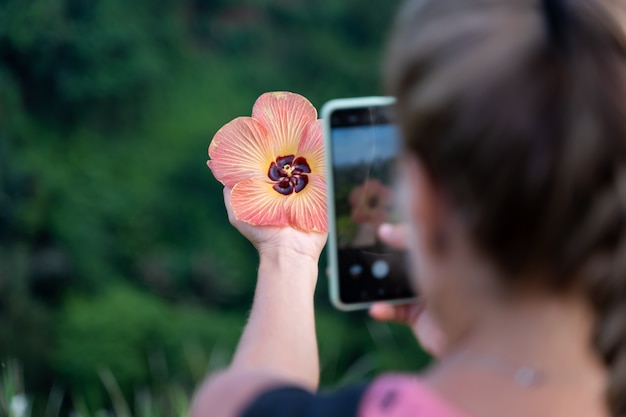Woman taking a picture with her mobile phone of a flower she is holding in her hand Free Photo