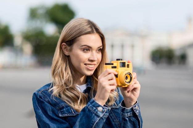 Donna che cattura una foto con sfondo sfocato fotocamera gialla Foto Gratuite