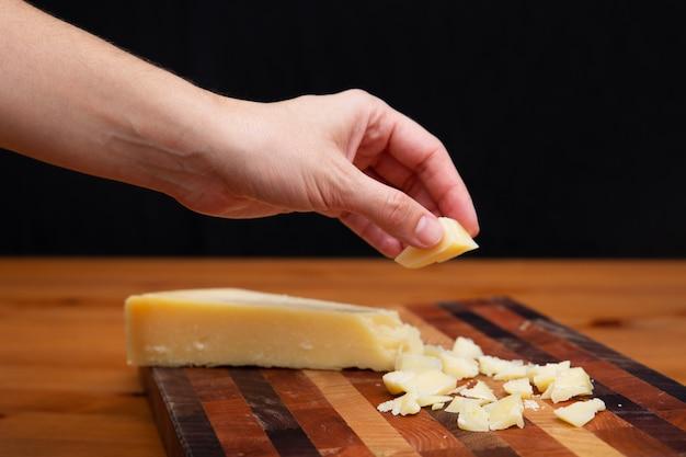 Donna che prende pezzo di parmigiano dal bordo di legno Foto Gratuite