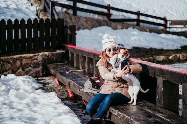Woman taking a self portrait with her cute dog outdoors. technology and pets concept Premium Photo