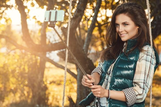 Woman taking selfie in autumn park Premium Photo