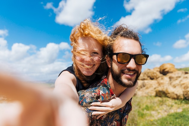 Woman taking selfie and sitting on back of man Free Photo