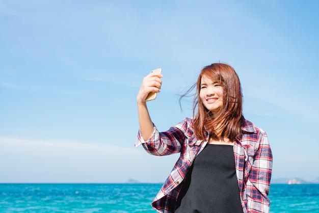 Woman taking selfie using smartphone at sea travel lifestyle. Premium Photo