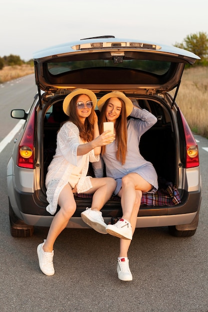Woman taking selfie while in the car trunk Free Photo