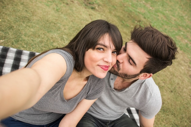 Woman taking selfie while her boyfriend kissing Free Photo