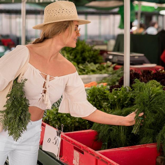 市場の場所からディルを取る女性 無料写真