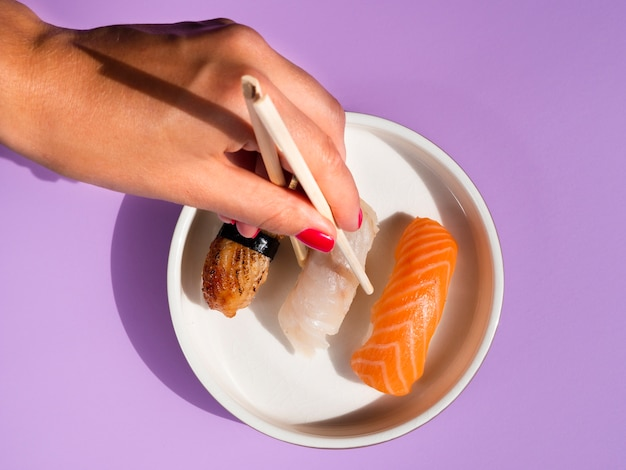 Woman taking a sushi from a white plate on blue background Free Photo
