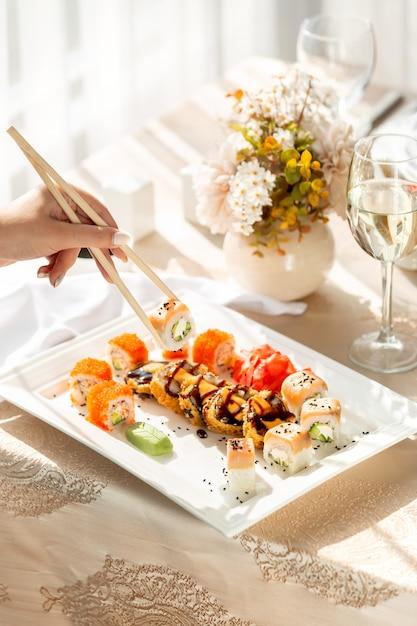 Donna che cattura i rotoli di sushi con le bacchette Foto Gratuite