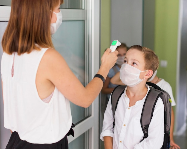 Woman taking the temperature of a kid Premium Photo