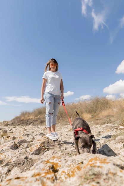 Woman taking a walk with her dog on the beach Free Photo