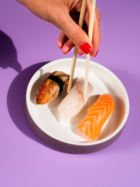 Woman taking with chopsticks sushi from a white plate Free Photo
