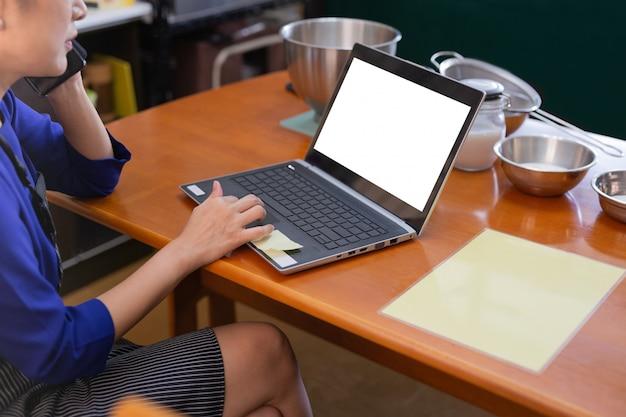 Женщина разговаривает по мобильному телефону и работает на ноутбуке с хлебобулочных ингредиентов на столе. Premium Фотографии