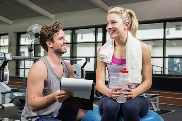 Woman talking to her trainer after a workout Premium Photo
