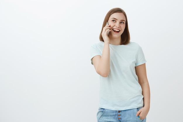 友達と楽しく話をしている女性は、電話に何時間もかけることができます。 tシャツ、ジーンズのポケットに手を握り、笑顔で脇を見つめて耳の近くのsmarpthoneで社交的な幸せでリラックスしたかっこいい女性 無料写真